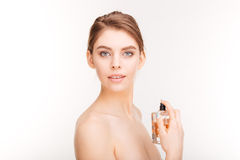 Pretty young woman holding bottle of parfume. Beauty portrait of pretty young woman holding bottle of parfume over white background royalty free stock image
