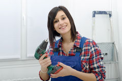 Pretty young woman holding  cordless drill. Pretty young brunette woman holding cordless drill Royalty Free Stock Photography