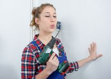 Pretty young woman holding cordless drill. Pretty young smiling woman holding cordless drill Stock Photo