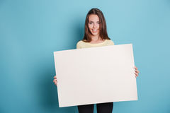 Pretty young woman holding empty blank board over blue background Royalty Free Stock Image