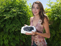 Pretty young woman holding fresh blueberries Royalty Free Stock Image