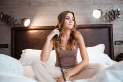 Pretty young woman holding handset sitting on bed Stock Image