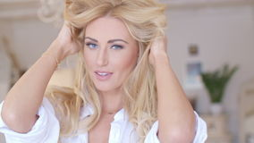 Pretty Young Woman Holding her Long Blond Hair. Close up Pretty Young Woman in White Shirt Holding her Long Blond Hair While Looking at the Camera stock video