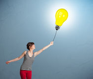 Pretty lady holding a light bulb balloon Stock Photography