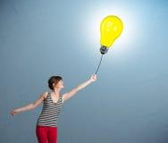 Pretty lady holding a light bulb balloon. Pretty young woman holding a light bulb balloon Stock Photography