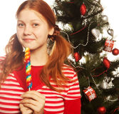 Pretty young woman  holding lolly pop. Christmas tree. Royalty Free Stock Photos