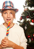 Pretty young woman  holding lolly pop. Christmas tree. Royalty Free Stock Images