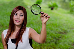 Pretty young woman holding a magnifying glass. Pretty young Asian woman holding aloft a magnifying glass with a smile outdoors in the country in a concept of Royalty Free Stock Photo