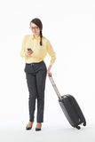 Pretty young woman holding a mobile phone and a suitcase Royalty Free Stock Photo