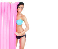 Pretty young woman holding pink inflatable mattress. Stock Images