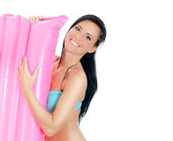 Pretty young woman holding pink inflatable mattress. Stock Photography
