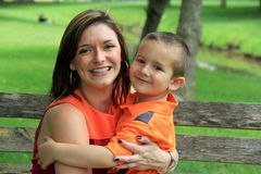 Pretty young woman holding smiling son on bench royalty free stock photography