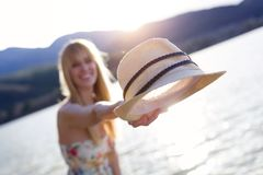 Pretty young woman holding straw hat on her hand and smiling at the camera on the pier near the lake. Stock Image