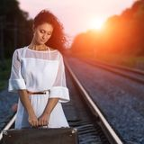 Pretty young woman holding a suitcase Royalty Free Stock Photos