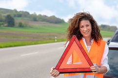 Pretty young woman holding a traffic warning sign Stock Image