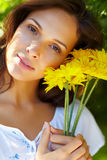 Pretty young woman holding yellow flowers Stock Photo