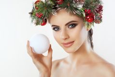 A pretty young woman holds in her hand a Christmas ball, on her head a beautiful wreath of spruce with cones and balls royalty free stock photo