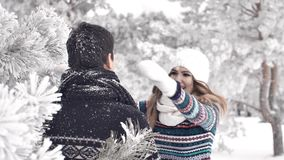 Pretty young woman hugging boyfriend in the winter woods.