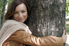 Pretty young woman hugging tree in a park Stock Image