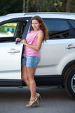 Pretty young woman with ignition key standing near own car, full-length Royalty Free Stock Image