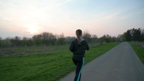 Pretty young woman jogging outdoors. Wearing sport outfit, running in the fields stock footage