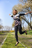Pretty young woman jumping on green grass. And smiling full of joy and vitality in summer or spring Royalty Free Stock Photography