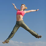 Pretty young woman is jumping outdoors Royalty Free Stock Images