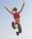 Pretty young woman is jumping outdoors Royalty Free Stock Image