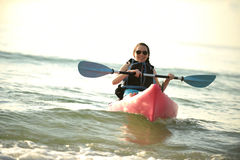 Pretty young woman kayaking in ocean Royalty Free Stock Photos