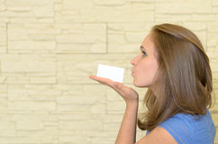 Pretty Young Woman Kissing a Blank Card on Hand Royalty Free Stock Image