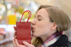 Pretty young woman kissing her Christmas gift Royalty Free Stock Images