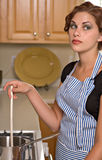 Pretty young woman in kitchen. Pretty, bored young woman cooks dinner in her kitchen stock image