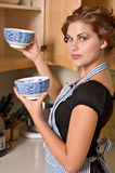 Pretty young woman in kitchen stock photography