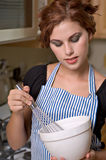 Pretty young woman in kitchen. Pretty young woman cooks dinner in her kitchen royalty free stock photography