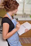 Pretty young woman in kitchen Stock Images