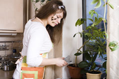 Pretty young woman on kitchen preparing dinner Royalty Free Stock Images