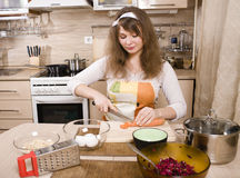 Pretty young woman on kitchen preparing dinner Royalty Free Stock Photos