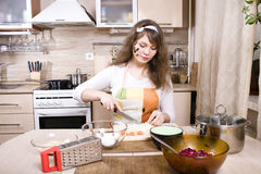 Pretty young woman on kitchen preparing dinner Stock Photo