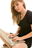 Pretty young woman with a laptop. A pretty young woman works on a laptop (isolated against white background stock photography