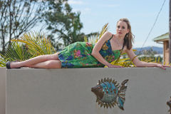 Pretty young woman laying on wall Royalty Free Stock Photography