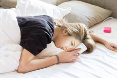 Pretty young woman lazy looking to phone while lying on bed royalty free stock images