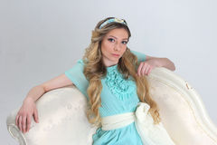Pretty young woman leaned back on white sofa Royalty Free Stock Image