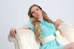 Pretty young woman leaned back on white sofa Royalty Free Stock Photos
