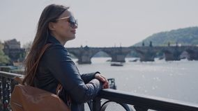 Pretty young woman in a leather jacket with a backpack standing at the river promenade terrace on beatiful sunny day. Famous Charles Bridge on the background stock footage