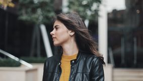 Pretty young woman in the leather jacket is walking near the business center. The girl fixes her hair looks around the stock footage