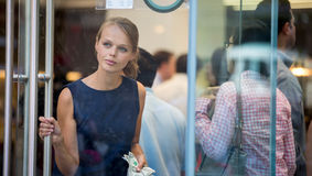Pretty, young woman leaving a store/restaurant Stock Images