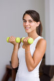 Pretty young woman lifting dumbbells Stock Photo