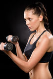 Pretty young woman lifting dumbbells in sportswear Stock Photos