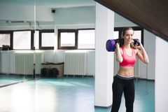 Young woman lifting weight in the gym. Pretty young woman lifting weight in the gym Stock Photo
