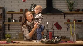 Pretty young woman lifts up the baby in her arms standing in modern kitchen showing to son bright red Christmas tree toy stock video footage